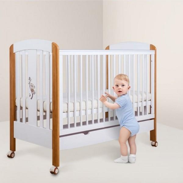 Ξύλινη κούνια μωρού σε λευκό χρώμα με καφέ λεπτομέρειες